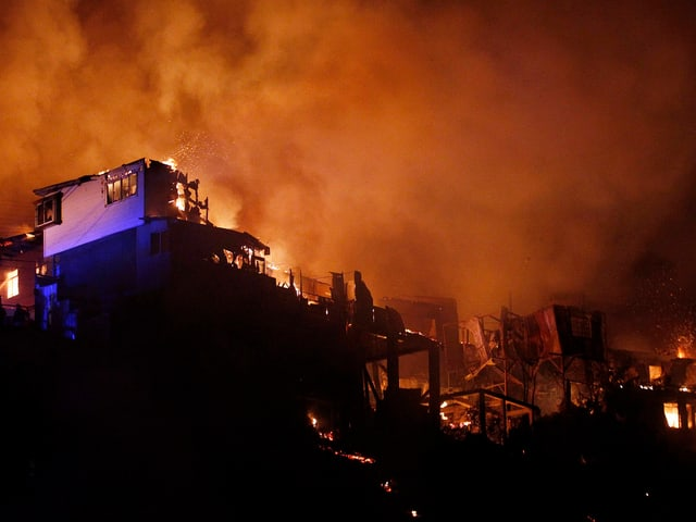 Brennende Häuser auf einem Hügel.