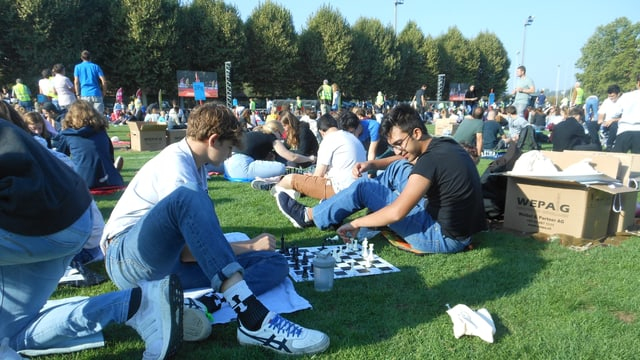 Man sieht zwei Jugendliche, die Schach spielen. Sie sitzen auf dem Fussballfeld auf dem Bode.