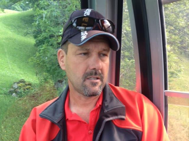 Mann mit Baseball-Kappe sitzt in einer Gondelbahn.
