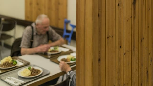 Persuna veglia davos in esch che mangia vid ina maisa.