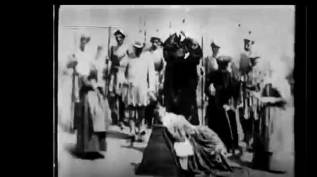 Szene aus einem alten Film: Ein Henker hebt ein Beil, vor ihm kniet eine Frau. Darum herum eine Menschenschar.