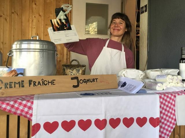 Käseproduzentin Rona Diem steht in ihrem improvisierten Marktstand für die Abholung ihrer bestellten Ware bereit.