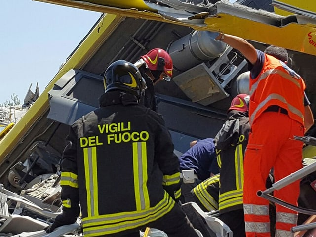 Helfer suchen in den Trümmerteilen nach Überlebenden des Unglücks