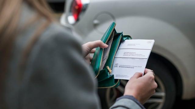 Frau steckt Führerschein in Brieftasche