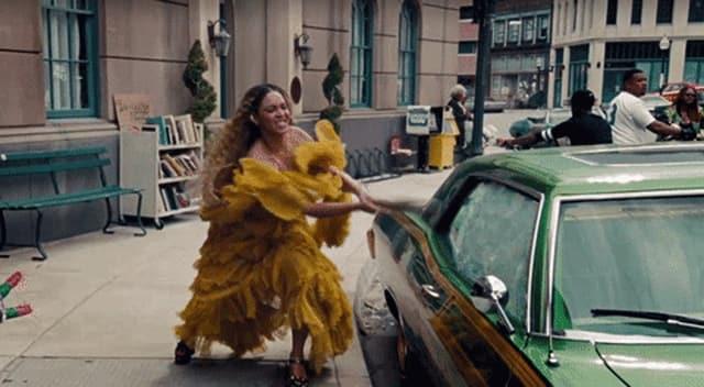 Frau schlägt eine Autoscheibe mit einem Baseballschläger ein.