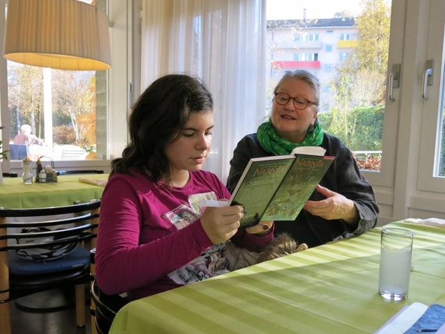 Eine Rentnerin liest mit einer Schülerin an einem Tisch ein Buch.