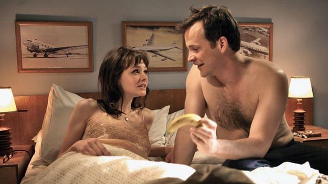 Ein Mann und eine Frau liegen im Bett.