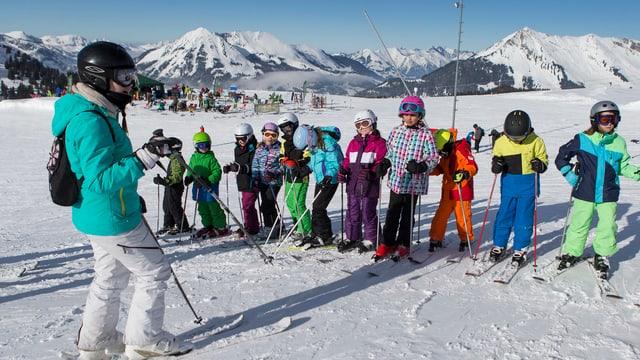 Scolasta ed uffants en la scola da skis.