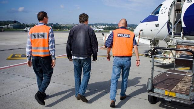 Ein Mann wird von zwei Polizisten in ein Flugzeug gebracht.