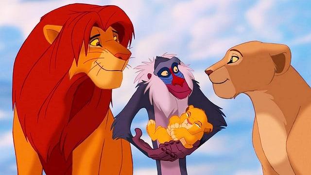 Ein Affe steht zwischen einem Löwenpärchen und hält ein Löwenbaby im Arm.