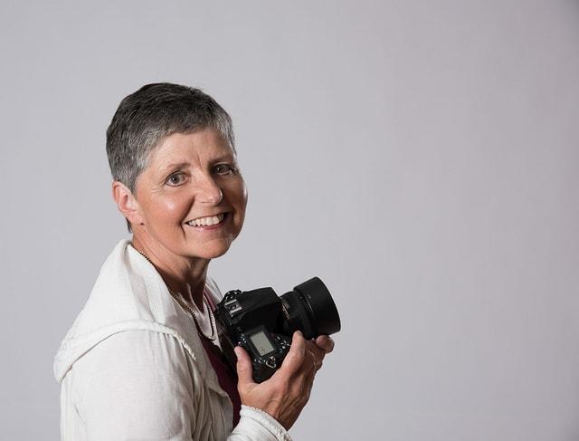 Ida Sgier la fotografa cun ina camera enta maun.