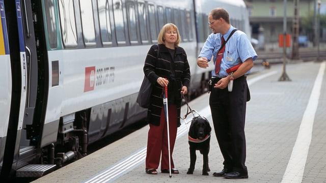 Blinde Frau und Zugführer sprechen vor Zug miteinander