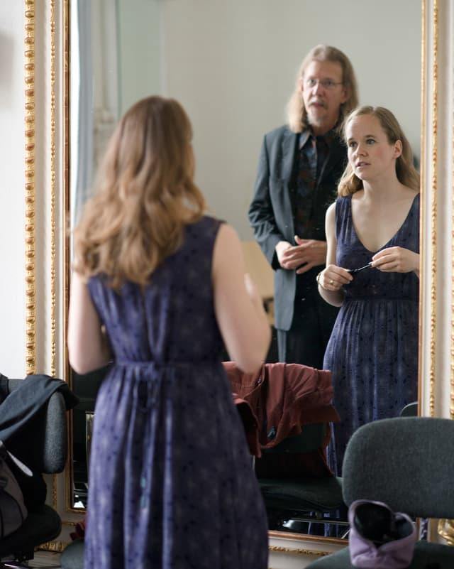 Eine Frau in einem eleganten Kleid und ein Herr vor einem grossen Spiegel.