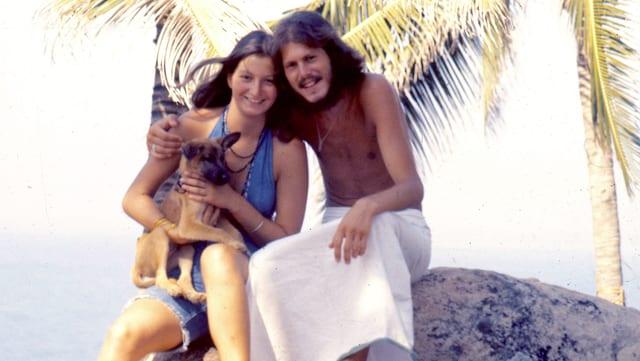 Ein junges Paar am Strand. Die junge Frau hält
