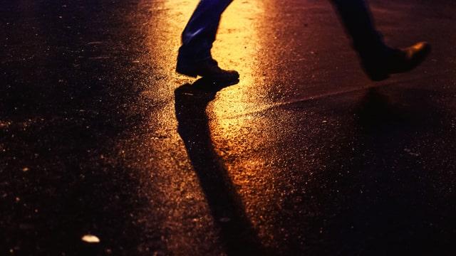 Füsse einer Person, die bei Nacht über Strasse geht