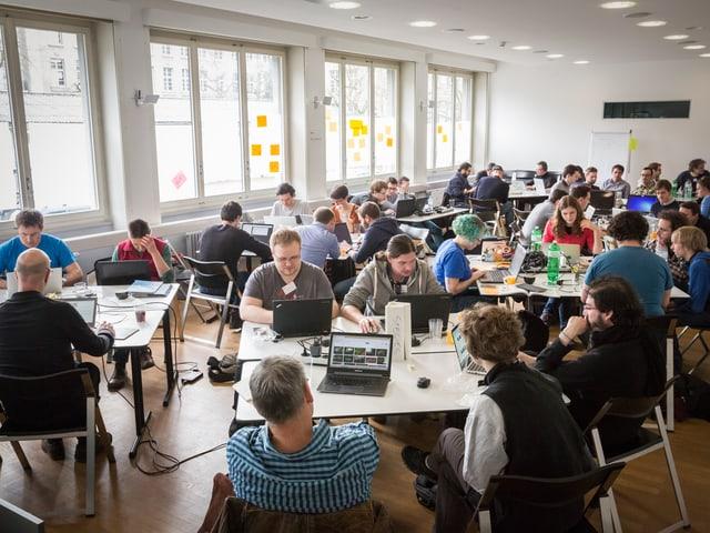 Auf engem Raum sitzen rund 40 Personen an Tischen über ihre Laptops gebeugt.