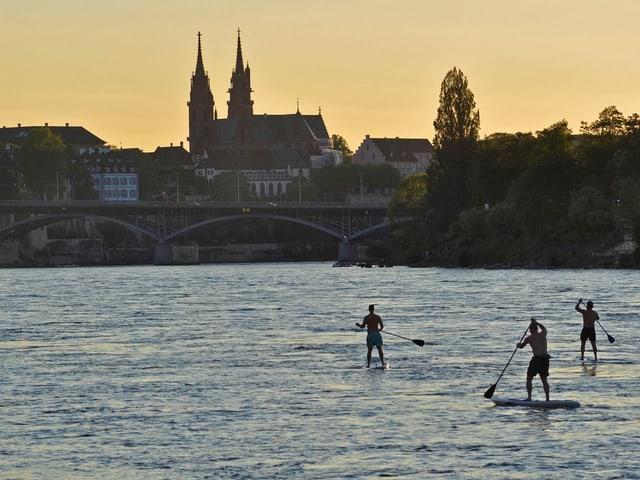 Stand Up Paddler auf dem Rhein mit dem Basler Münster im Hintergrund.