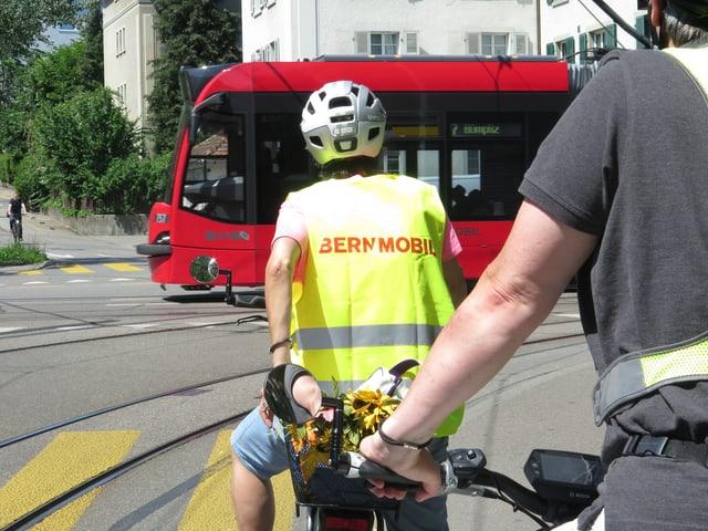 Velofahrerin hält. Tram fährt vorbei.