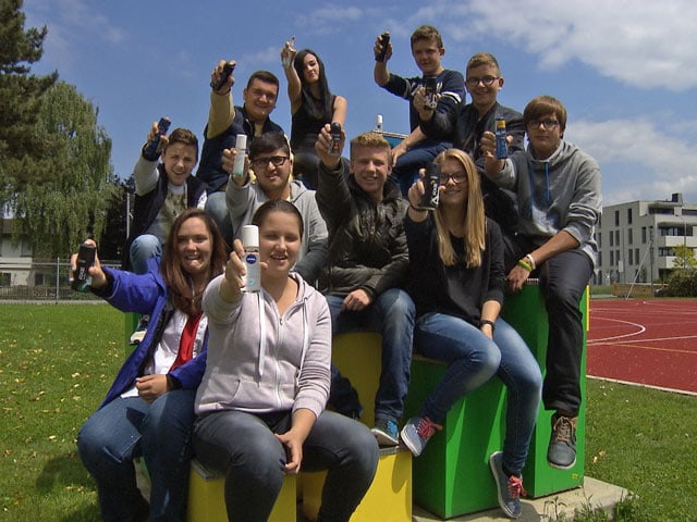 Elf Teenager sitzen auf einer Wiese und halten Deos in die Kamera.