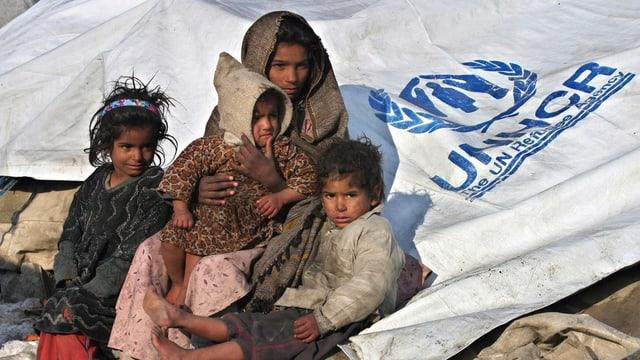 Kinder in schmutzigen Kleidern vor einem Flüchtlingszelt der UNHCR