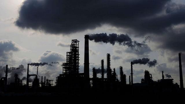 Eine Zemetfabrik in China mit qualmenden Schloten und dunklen Wolken darüber.