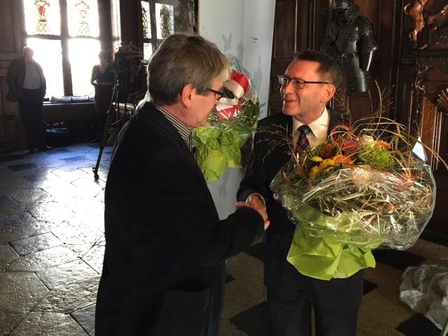 Zwei Politiker schütteln die Hand mit Blumensträussen in der Hand