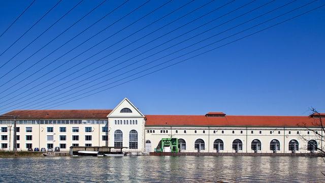 Fluss mit Wasserkraftwerk vor blauem Himmel mit Stromleitungen.