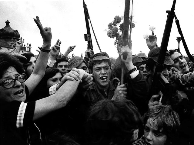 Schwarz-weiss-Bild von Soldaten und Bürgern, die mit Gewehren und Blumen auf der Strasse feiern.
