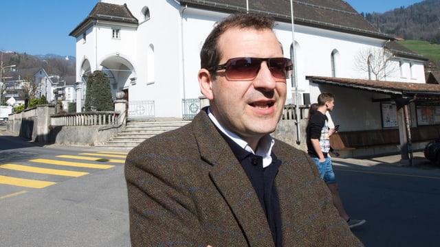 Gracia steht mit Sonnenbrille und verschränkten Armen in einem braunen Kittel vor einer Kirche.