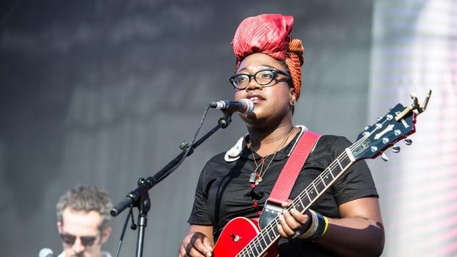 Eine Frau steht auf der Bühne mit einer roten Gitarre