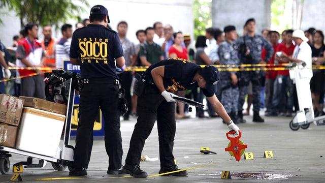 Polizeibeamte sichern den Tatort vor einer Flughafenhalle.