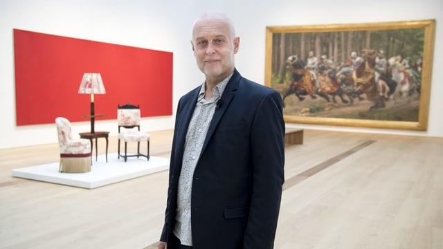 Ein Herr im Anzug steht in einem Ausstellungsraum, hinter ihm ein Gemälde und Möbel