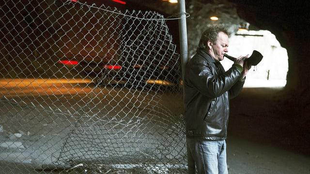 Ein Mann spielt Ziegenhorn in nächtlicher Umgebung.