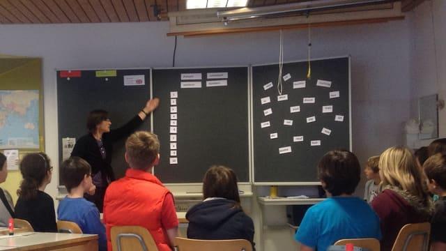 Ina classa da scola rumantscha durant l'instrucziun da franzos. La scolasta mussa insatge alla tavla.
