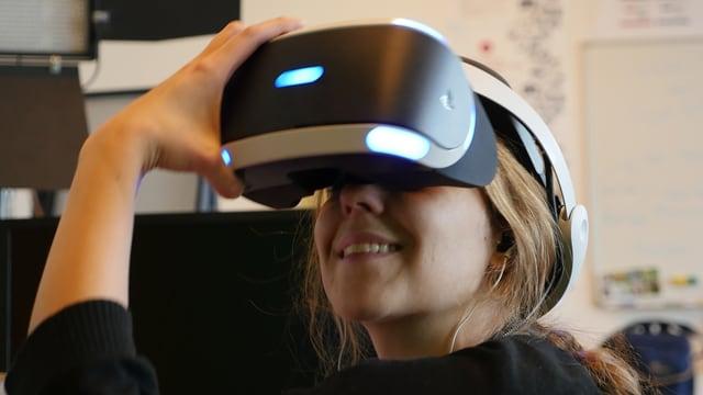 Eine Frau trägt eine Virtual-Reality-Brille von Playstation.