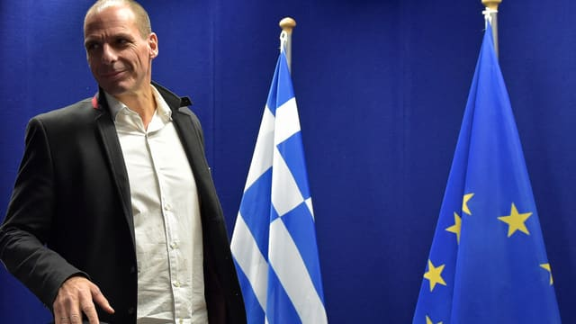 Yanis Varoufakis il minister da finanzas da la Grezia sper las bandieras da la Grezia e da l'UE