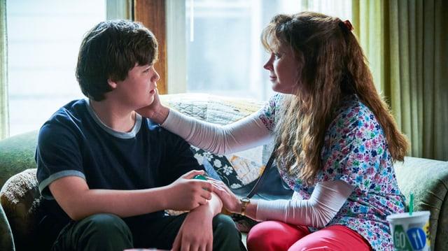 Filmszene: Ein Teenager und eine Frau sitzen auf dem Sofa, sie streicht ihm über die Wange.