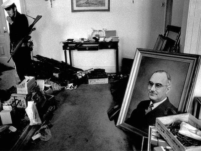 Ein verlassener Raum, bewacht von einem Marinesoldten – ein Porträtbild von Marcelo Caetano steht auf dem Boden.