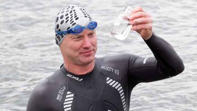 Chemieprofessor Andreas Fath hält Plastikfläschchen in der Hand.