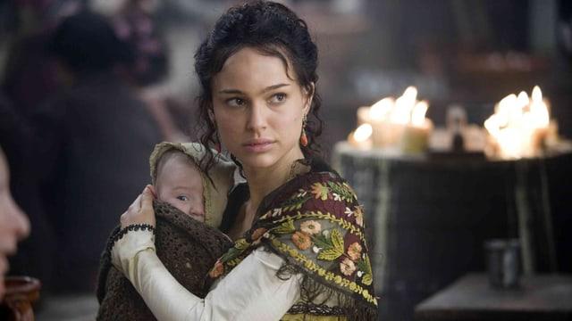 Nathalie Portmann als Ines hält ein Kind im Arm.