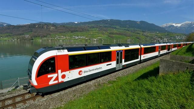 Zug der Zentralbahn fährt entlang eines Sees.