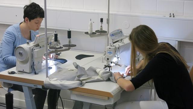 Zwei junge Frauen arbeiten an Nähmaschinen im Atelier «LU Couture»