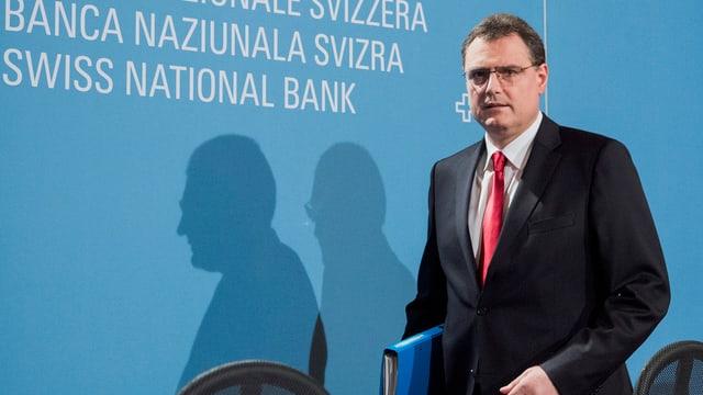 """Zu sehen ist SNB-Präsident Thomas Jordan im Anzug, stehend vor einer blauen Wand mit der Aufschrift """"Schweizerische Nationalbank"""""""