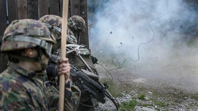 Soldaten in Kampfmontur verstecken sich hinter einem Haus, an dessen Vorderseite etwas explodiert.