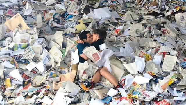Das Filmliebespaar küsst sich unter lauter Altpapier.