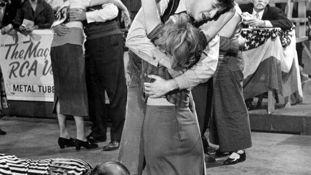 Ein Tanzpaar ist erschöpft und die Frau sinkt zu Boden