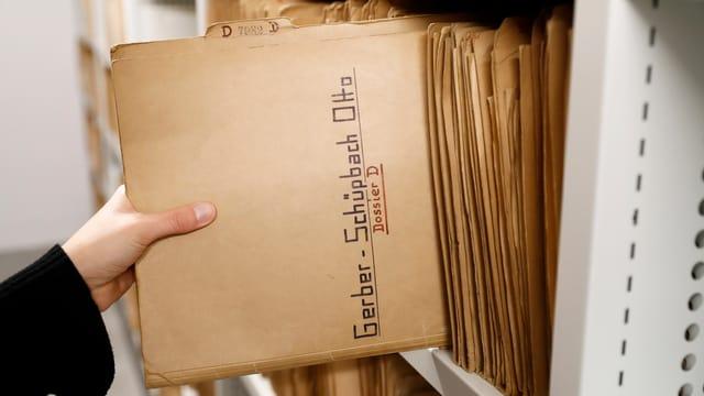 Eine Hand zieht ein Dossier aus einem Aktenschrank
