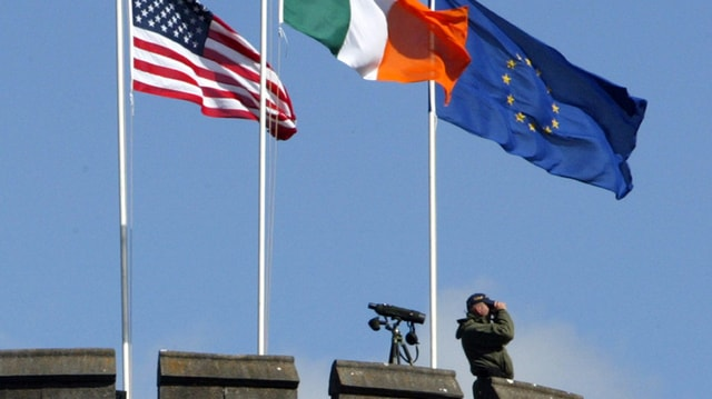 Drei Fahnen wehen im Wind: USA, Irland und EU. Ein Mann steht mit Feldstecher daneben und schaut in die Ferne.