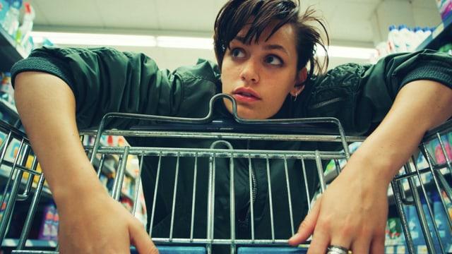 Junge Frau lehnt sich über Einkaufswagen.