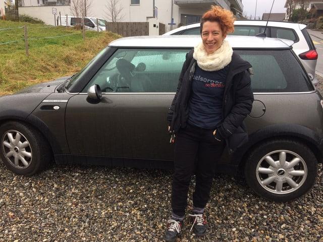 Frau vor Auto.